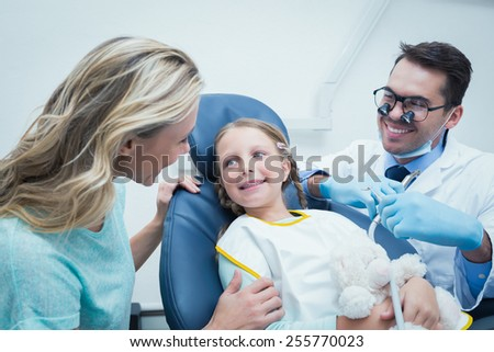 Dentist examining girls teeth in the dentists chair with assistant - stock photo