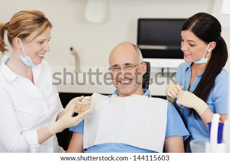 Dentist explaining teeth model to smiling male patient at clinic - stock photo