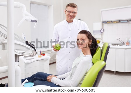 Dentist holding an apple in the clinic - stock photo