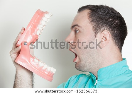 Dentist holding oversized false teeth dentures - stock photo