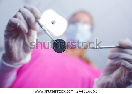 Dentist in surgical mask holding tools over patient at the dental clinic - stock photo