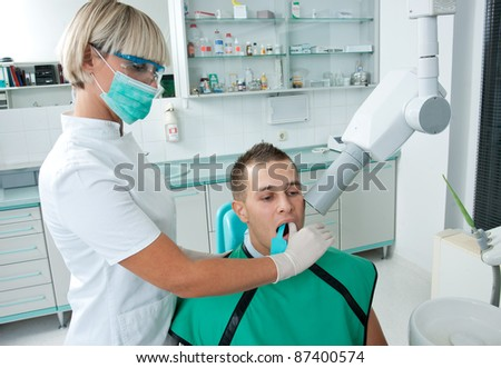 dentist making x-ray image of patient teeth - stock photo