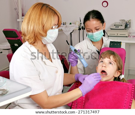dentist nurse and little girl patient in dental office - stock photo