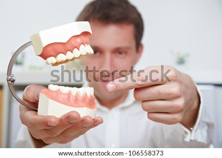 Dentist pointing with his index finger to oversized teeth model - stock photo