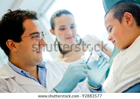 Dentist showing a boy how to brush his teeth - stock photo