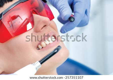 Dentist squeezes fillings in the mouth of the patient. Dentist makes the process of treatment of a beautiful young girl. Woman in protective glasses - stock photo