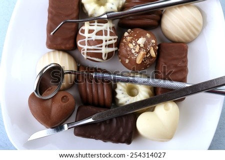 Dentist tools with sweets on plate close up - stock photo