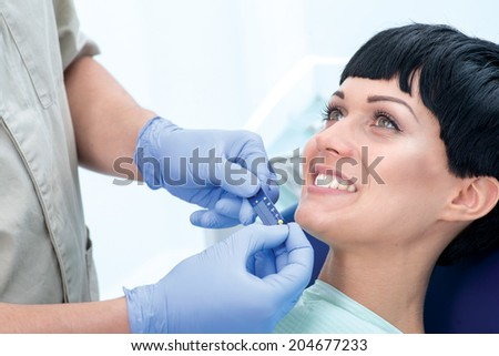 Dentist with a ruler measuring the length of the tooth canal. Dentist makes the process of treatment of a beautiful young girl. Woman smiling at her doctor. - stock photo