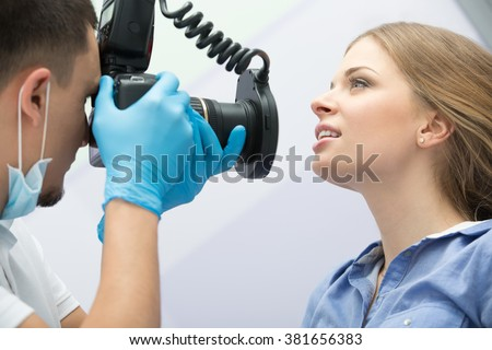 Dentist with camera making shots of patients smile after treatment. Special camera with flash ring shadowless. - stock photo