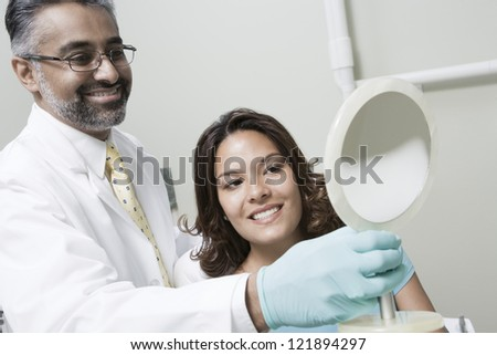 Dentist with female patient checking her teeth in the mirror - stock photo