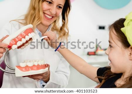 Dentist with little girl, explaining importance of dental hygiene - stock photo