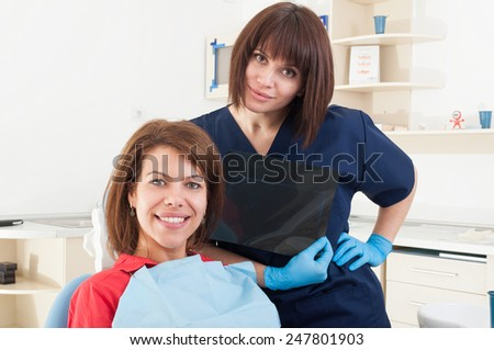 Dentist woman and smiling female patient sitting in dental chair - stock photo