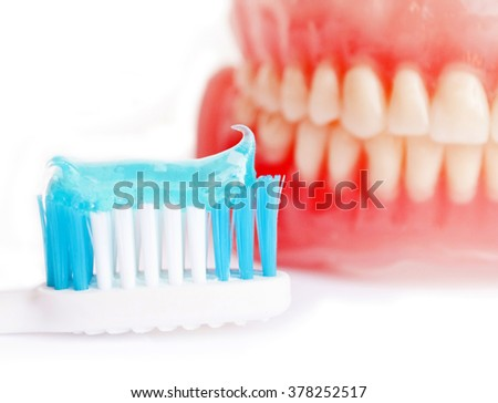 Denture and tooth paste isolated on white - stock photo