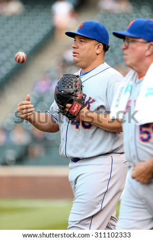 DENVER-AUG 21: New York Mets pitcher Bartolo Colon (L) and pitching coach Dan Warthen walk the field before a game against the Colorado Rockies at Coors Field on August 21, 2015 in Denver, Colorado. - stock photo