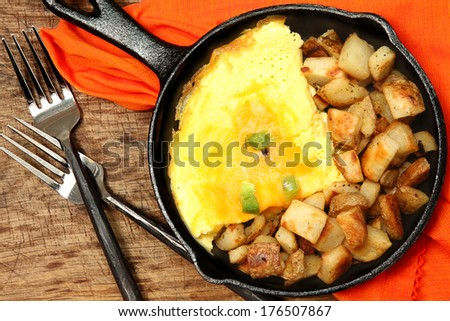 Denver Omelette and Ranch Potatoes in Cast Iron Skillet at Table - stock photo