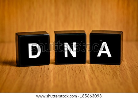 Deoxyribonucleic acid or DNA text on black block - stock photo