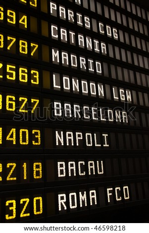 Departure board at an airport in Italy. Flights to Paris, Catania, Madrid, London, Barcelona, Napoli, Bacau and Rome. - stock photo