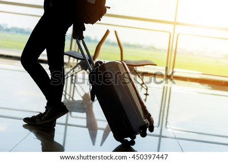 Departure lounge at the airport with traveller and luggage - stock photo