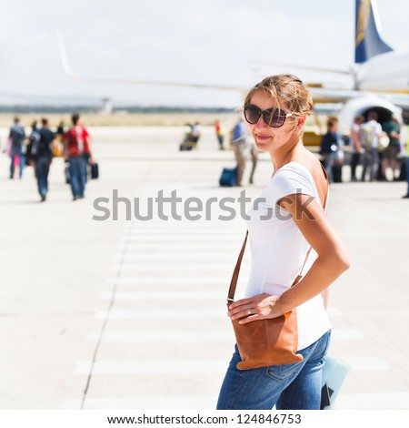 Departure - young woman at an airport about to board an aircraft on a sunny summer day - stock photo
