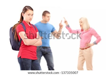 Deppressed teenager looking at camera with mother and father arguing in the background isolated on white background - stock photo