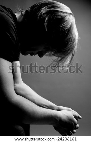Depressed blond man covering his face - stock photo