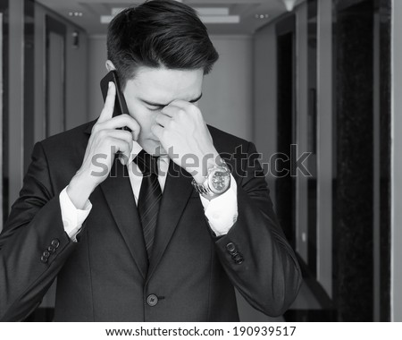 Depressed business man talking on the phone. Unemployment concept. - stock photo