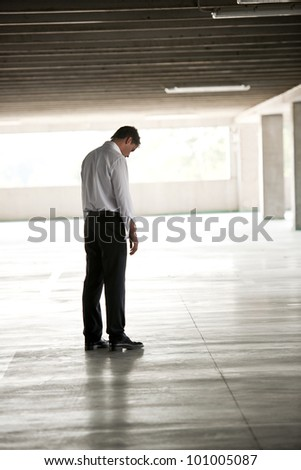 Depressed Businessman In Undeground Parking - stock photo