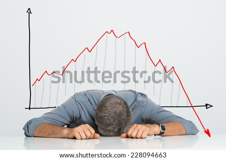 Depressed Businessman Leaning His Head Below a Bad Stock Market Chart - stock photo