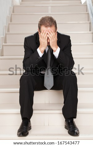 Depressed businessman. Sad mature man in formalwear covering face with hands while sitting on staircase  - stock photo