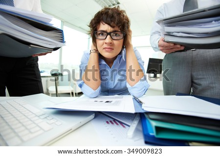 Depressed businesswoman has a lot of work with documents - stock photo