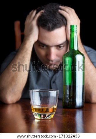 Depressed drunk man suffering a headache (on a black background) - stock photo