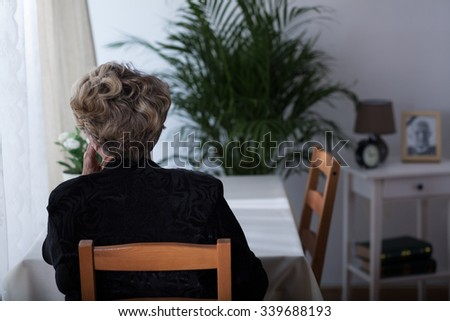 Depressed elderly widow sitting alone at home - stock photo