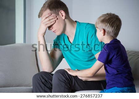 Depressed father sitting on couch with his son - stock photo