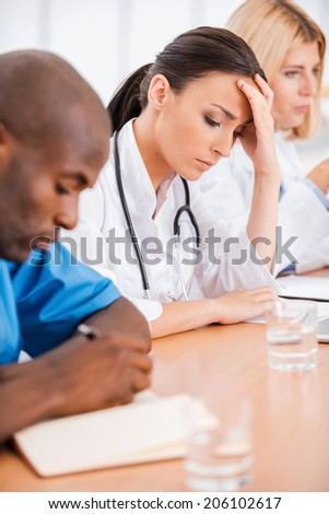 Depressed female doctor. Depressed young female doctor holding hand in hair while sitting together with her colleagues at the meeting - stock photo