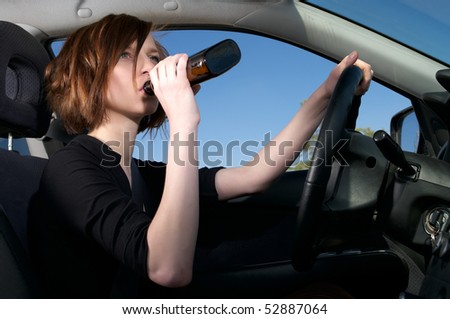 Depressed female driver drinking whiskey from a bottle - stock photo
