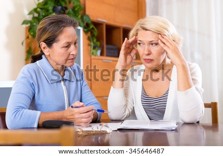 Depressed female pensioners discussing finances indoor. Focus on the left woman - stock photo