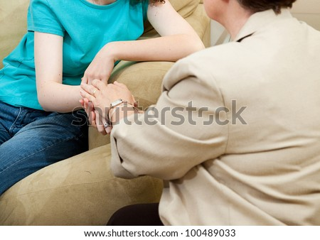 Depressed girl gets counseling and comfort from a caring therapist. - stock photo