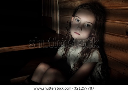 Depressed girl sitting in a dark hallway in home - stock photo