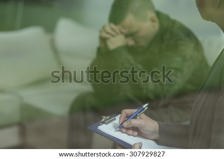 Depressed glum soldier during therapy of depression - stock photo
