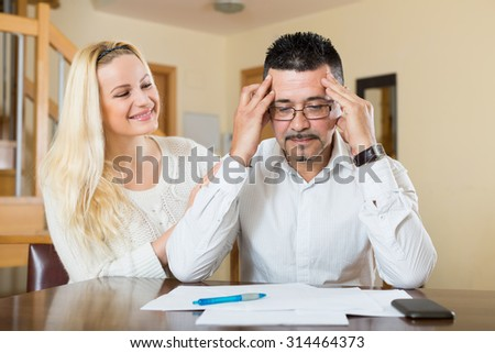 Depressed husband calculating invoices, wife reassuring him   - stock photo