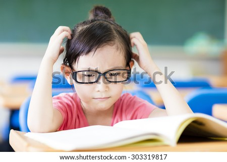 Depressed little girl study in the classroom - stock photo