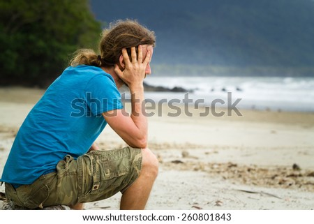 Depressed lonely man sitting at the beach - stock photo