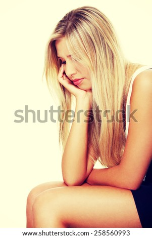 Depressed lonely woman sitting and thinking. - stock photo