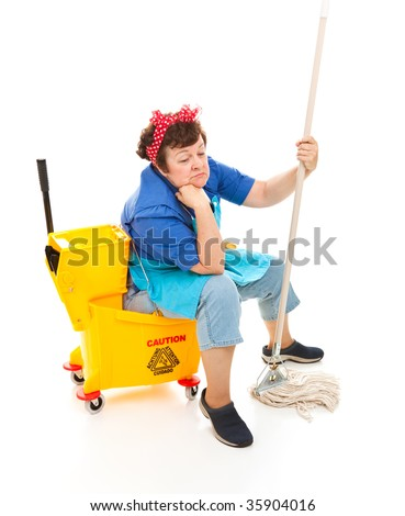 Depressed maid sitting in her bucket and holding her mop, with a sad expression on her face.  Full body isolated. - stock photo