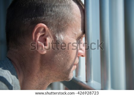 Depressed male inmate holds prison bars in despair - stock photo