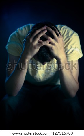 Depressed man sitting in the dark - stock photo