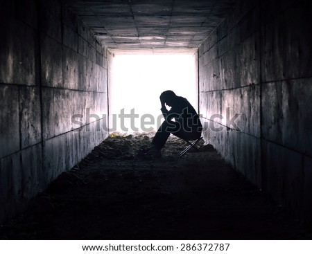 depressed man sitting in the tunnel - stock photo