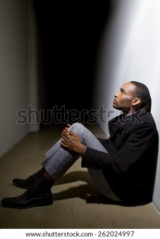 depressed man who lost faith sitting alone in a dark hallway - stock photo