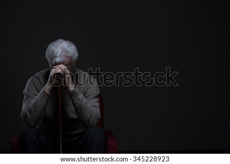 Depressed old man hiding his face behind hands - stock photo