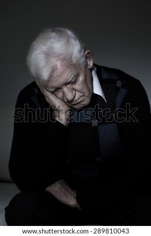 Depressed old man sitting alone in darkness - stock photo